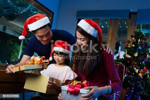 istock Asian family opening a gift box on christmas day happy 853303890