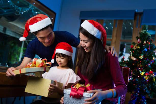 asiatischen familie öffnen einer geschenkbox am weihnachtstag glücklich - weihnachten japan stock-fotos und bilder