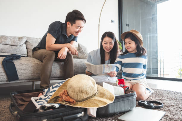 familia asiática embalaje bolsa/equipaje y la planificación de viajar en las vacaciones de verano - viaje a asia fotografías e imágenes de stock