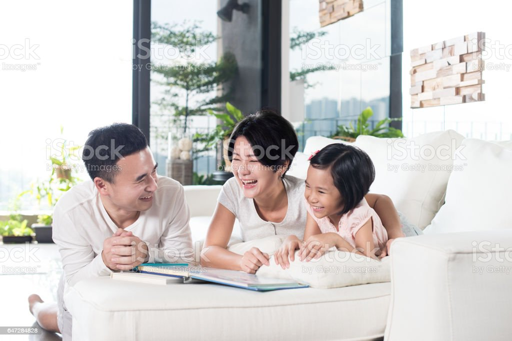 Asian family reading a book together at home. stock photo