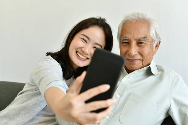 Asiatische Familienbeziehung, Tochter und älterer Vater mit Smartphone für Selfie zusammen, Senioren verbringen Zeit lernen, Social Media und digitale Technologie-Plattform zu verwenden. – Foto