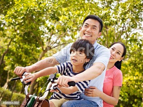 istock asian family riding bike in park 498864392