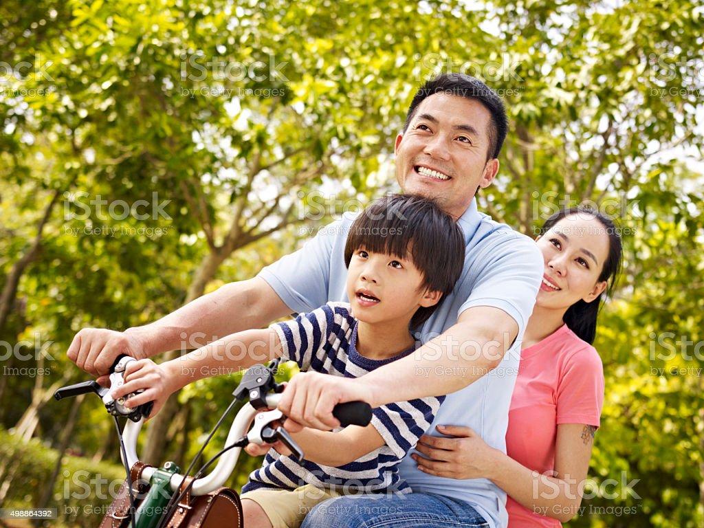 Famille asiatique équitation un vélo dans le parc - Photo