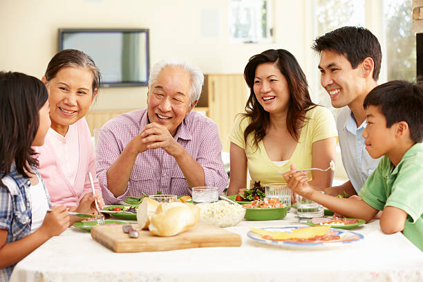 Asian family sharing meal at home stock photo