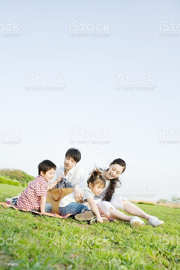 Asian family sitting in a field stock photo