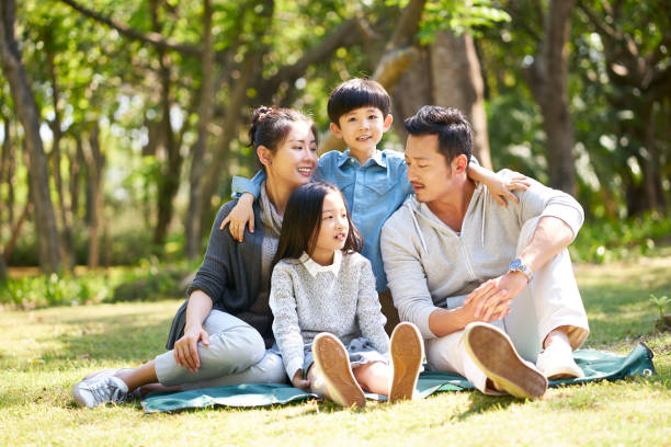 asian family sitting on grass talking chatting - east asian ethnicity stock photos and pictures