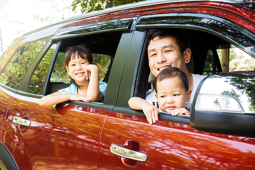 istock Asian family smiling in red car, action at window car. Father and two daughter happiness emotion. 939652896