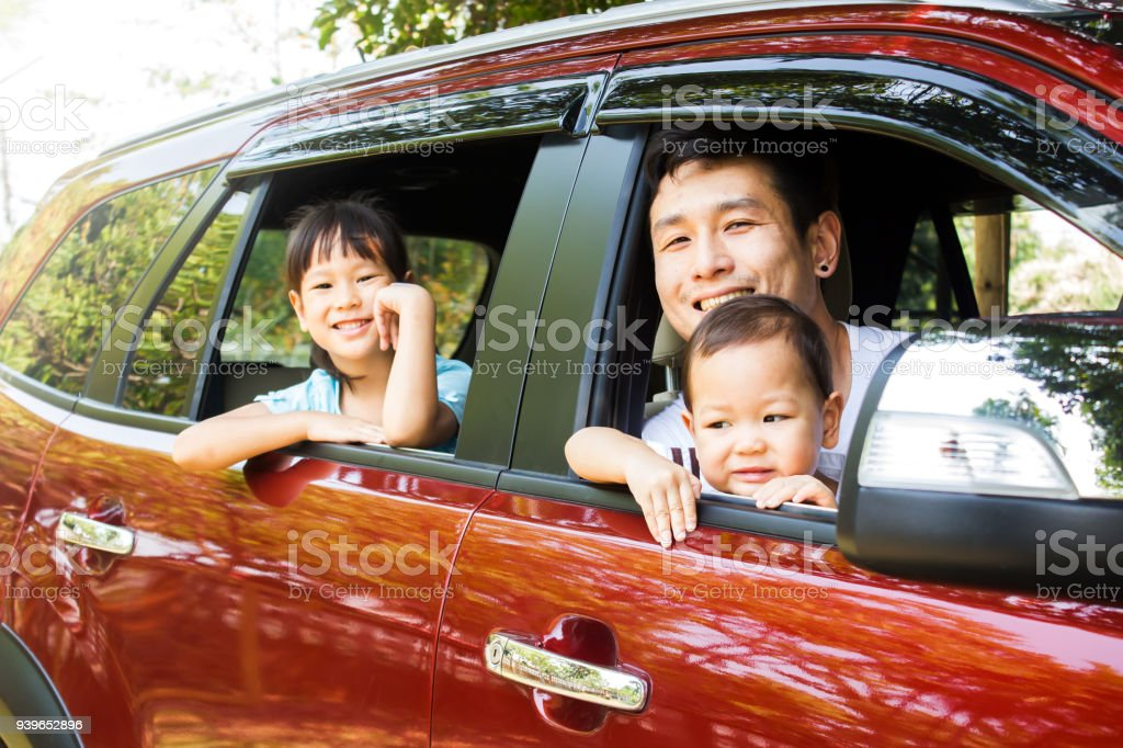 Asian family smiling in red car, action at window car. Father and two daughter happiness emotion. stock photo