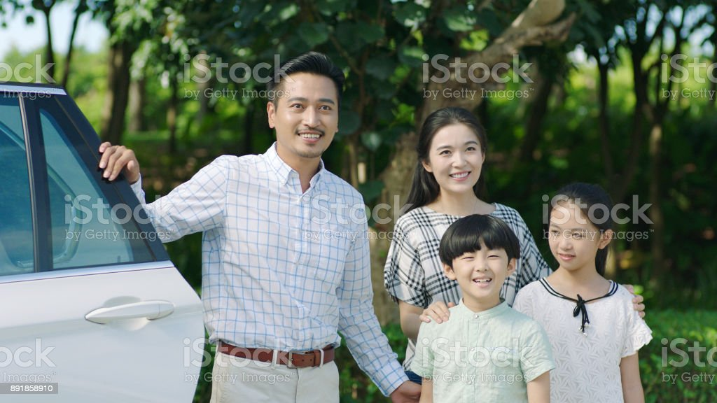 Asian family standing beside car, looking forward and smiling stock photo
