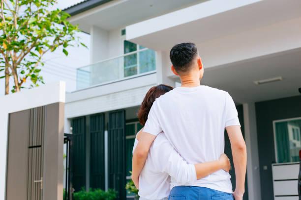 Asiatische Familie draußen mit ihrem neuen Haus und Auto, Boxen – Foto
