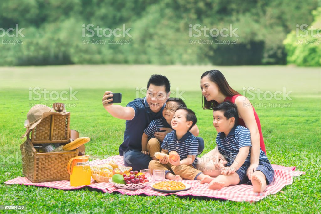 Asian family taking a picture in the park stock photo