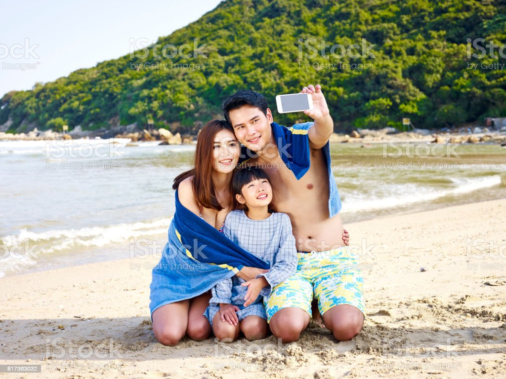 asian family taking a selfie on beach stock photo