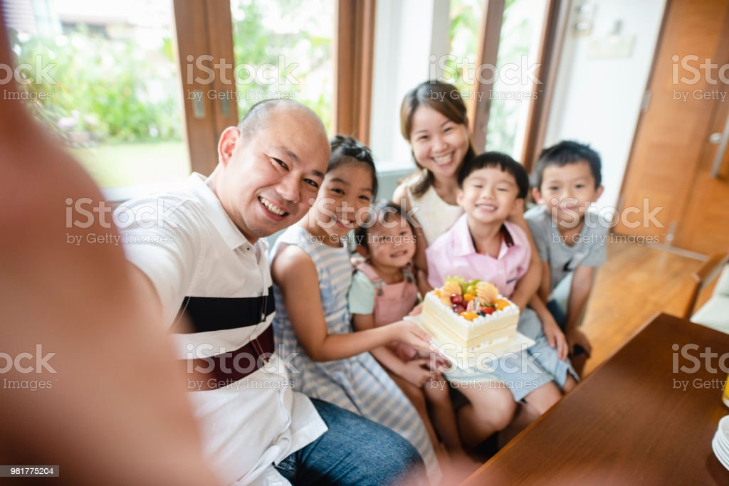 Asian family taking a selfie with birthday cake stock photo