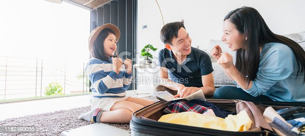 istock Asian Family travel concept happiness dad mom daughter packing stuff  cloths and planing for vacation road trip with exited and joyful 1182160035