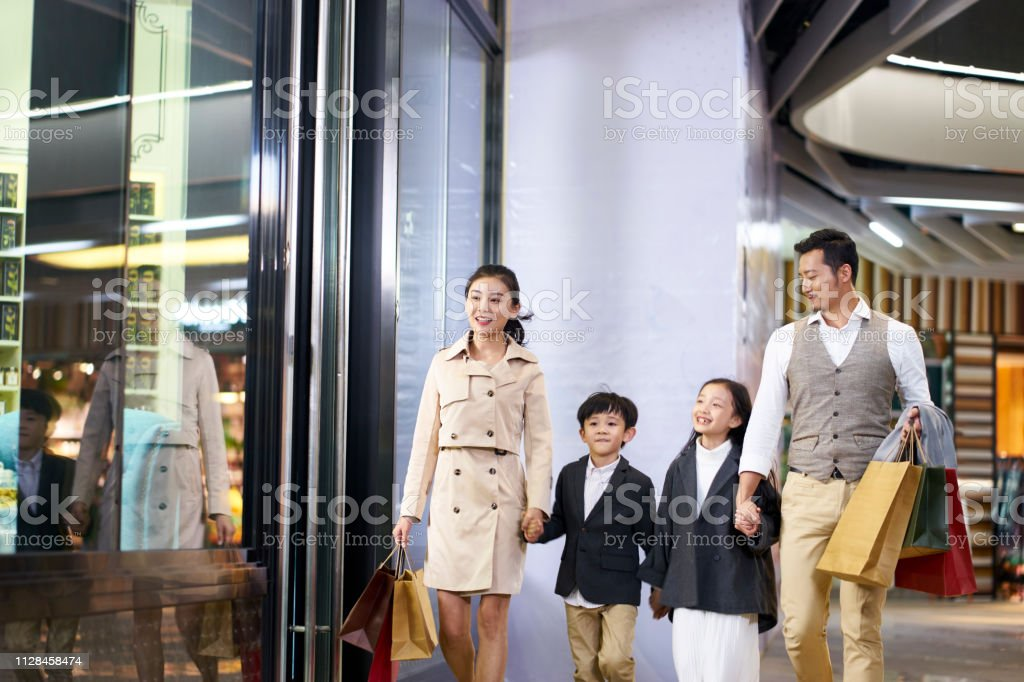asian family walking in shopping mall stock photo