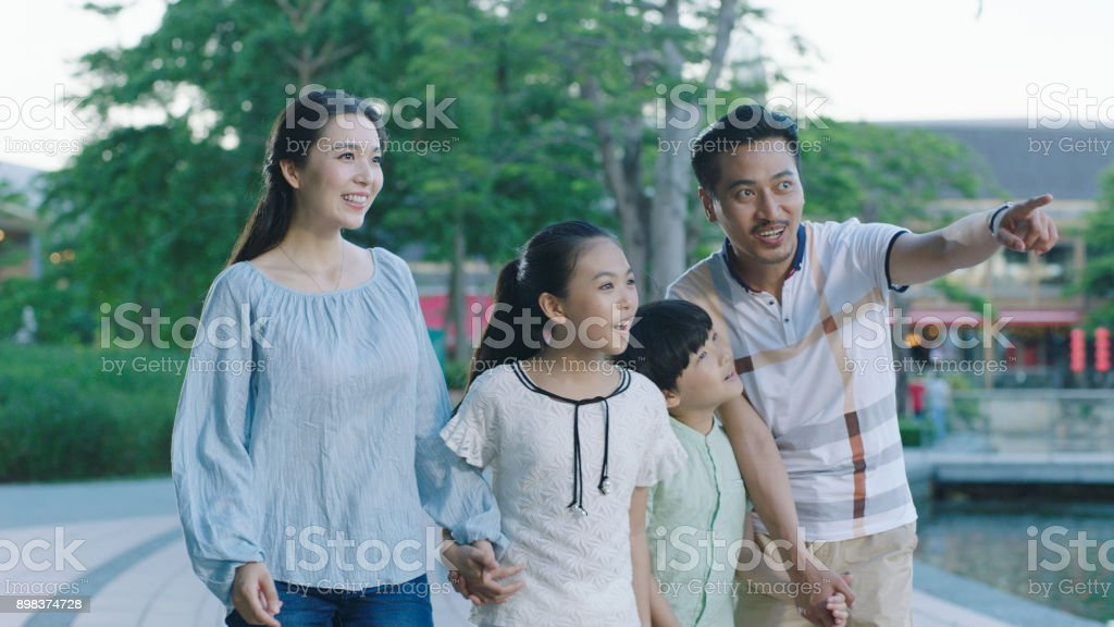 Asian family walking together on promenade, excited when looking ahead stock photo