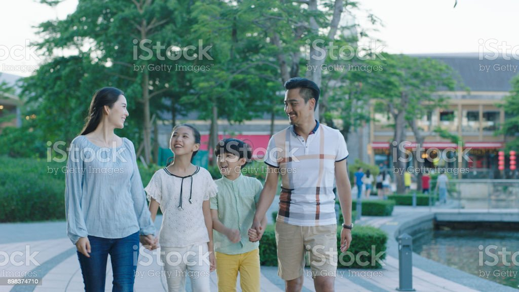 Asian family walking together on promenade, excited when looking at each other stock photo