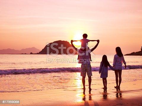 istock asian family watching sunrise on beach 817359058