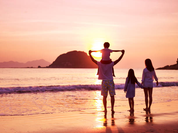 asian family watching sunrise on beach - vacanze foto e immagini stock