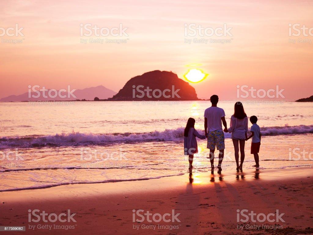 ビーチで日の出を見てアジアの家族 ストックフォト