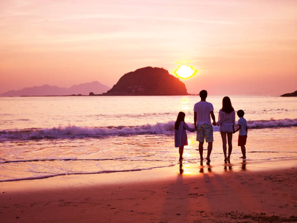 asian family watching sunrise on beach - singapore nature stock photos and pictures