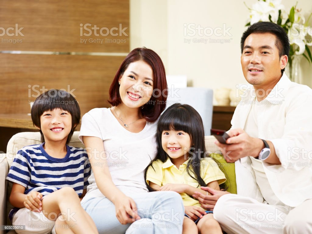 asian family watching TV together at home stock photo