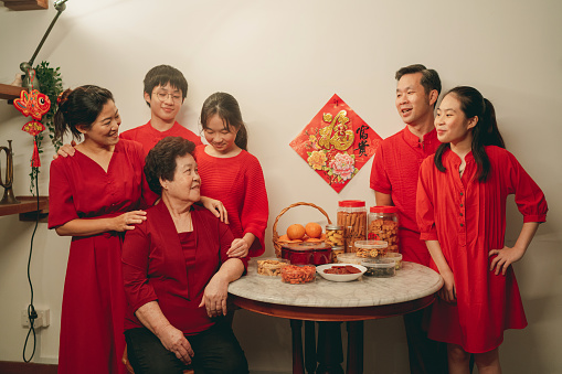 Asian family wearing red candidly standing around a table with Chinese New Year table before taking the family portrait photo