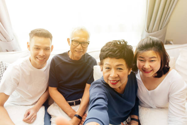Asian family with adult children and senior parents taking selfie and sitting on a sofa at home. Happy and relaxing family time stock photo