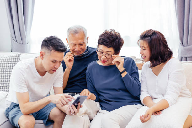 Asian family with adult children and senior parents using a mobile phone and relaxing on a sofa at home together Asian family with adult children and senior parents using a mobile phone and relaxing on a sofa at home together old mother son asian stock pictures, royalty-free photos & images