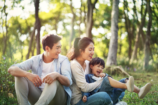 asian family with one child having fun in the woods stock photo