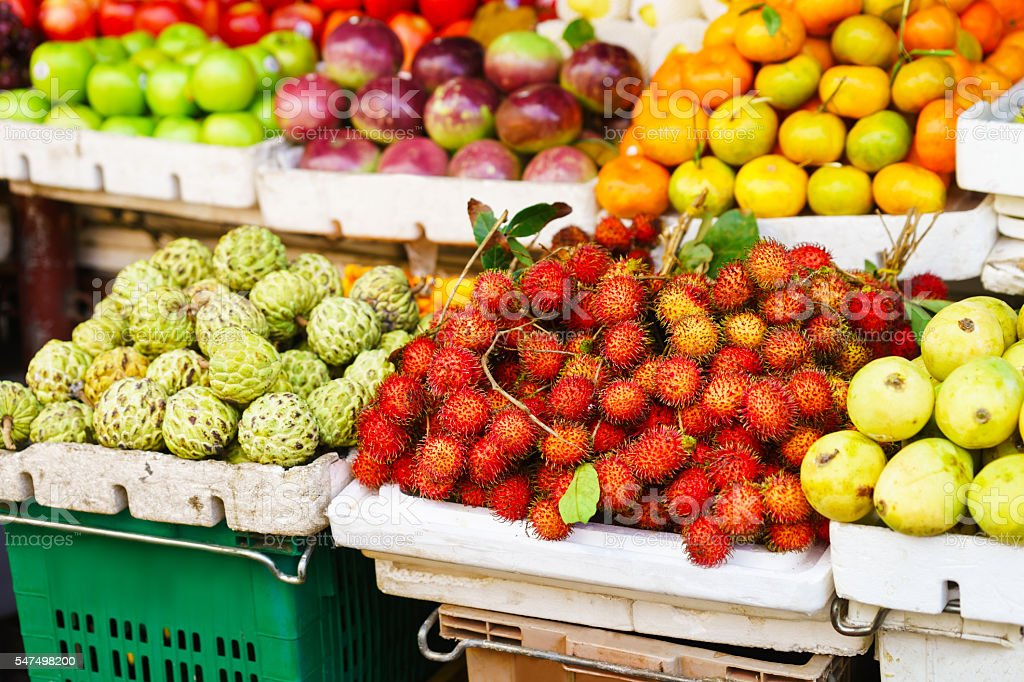 Asian farmer market selling Passion fruit and cherimoya and other stock photo