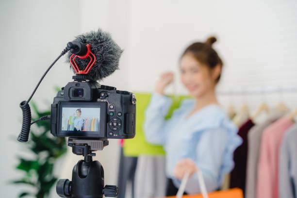 Asiatische Mode-Bloggerin Online-Influencer mit Einkaufstaschen und viele Kleidung auf Kleiderständer für die Aufnahme neuer Mode-Video-Übertragung Live-Video an soziale Netzwerk per Internet zu Hause übertragen. – Foto