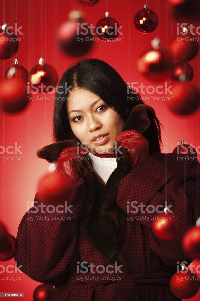 A young Asian Chinese fashion model in winter fashion in a red...