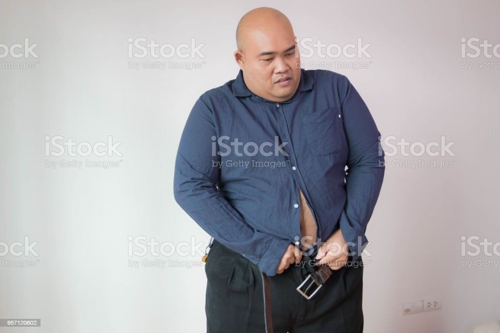 Asian fat man fasten small size of shirt stock photo