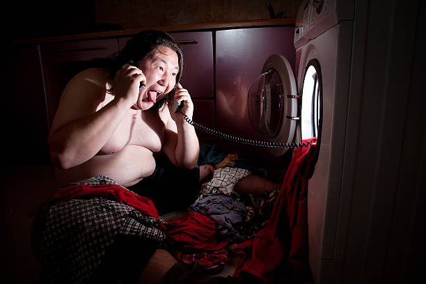 Asian fat man near washing machine stock photo