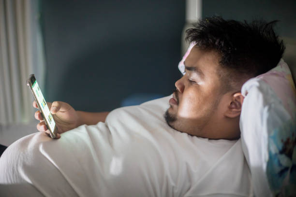 Asian fat man using a phone before sleep stock photo