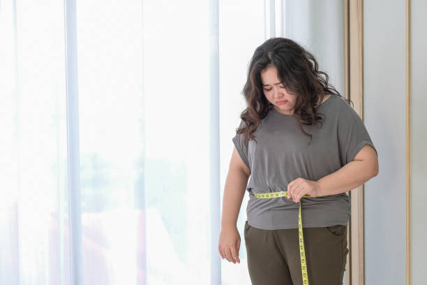 Asian fat women are sad because of the increase in size after checking with a tape measure.