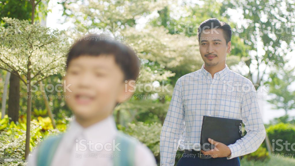 Asian father accompnying his son going to school in the morning stock photo