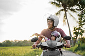 asian father and child look at sunset while riding motorbike scooter