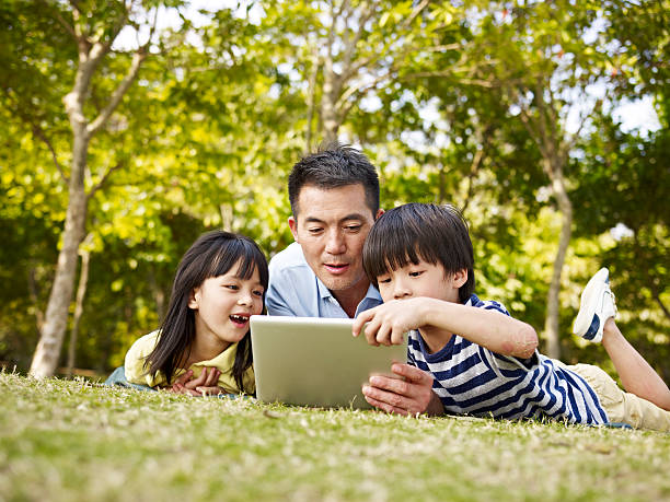 asian father and children using tablet computer outdoors - singapore nature stock photos and pictures
