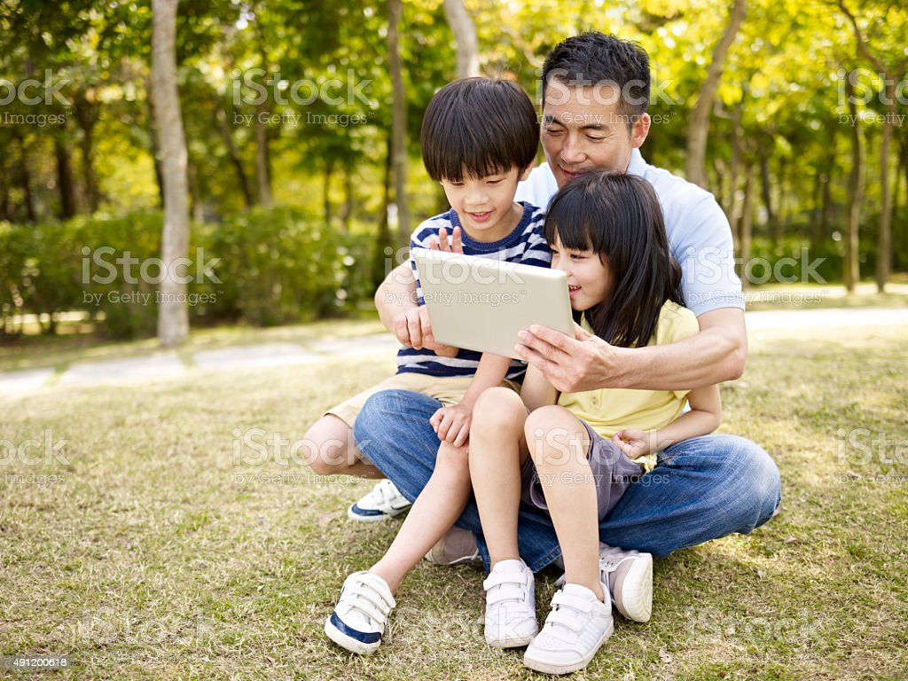asian father and children using tablet outdoors stock photo