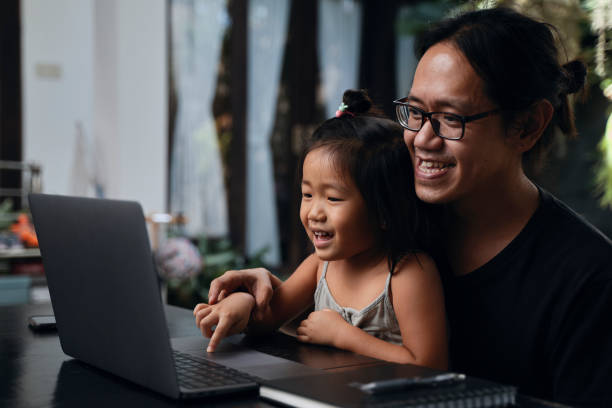 asian father and daughter interacting in front of laptop at home - young girl computer home front imagens e fotografias de stock