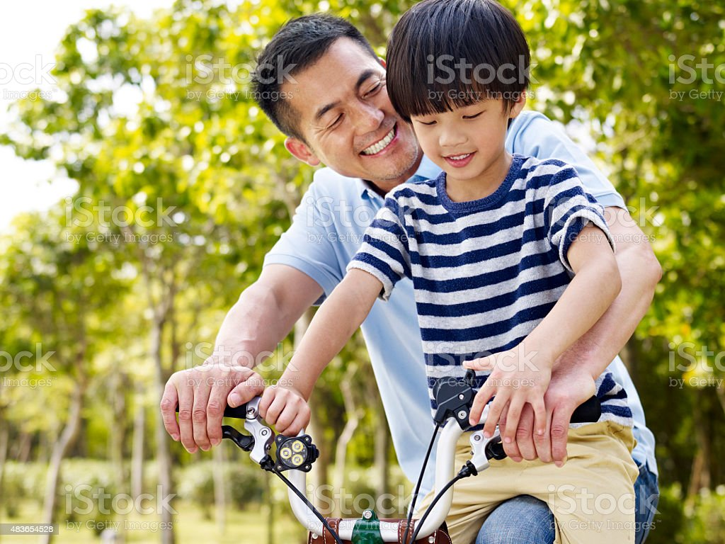 asian father and son enjoying biking outdoors stock photo