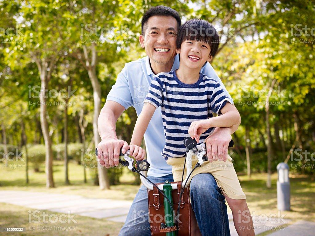 asian father and son enjoying biking outdoors stock photo