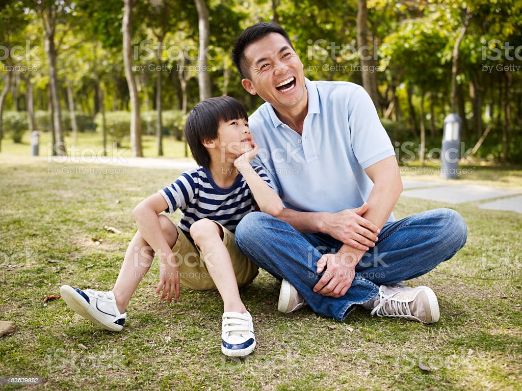 asian father and son having a conversation stock photo