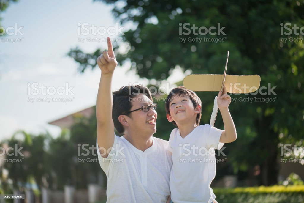 Asian father and son playing cardboard airplane together in the park outdoors royalty-free stock photo