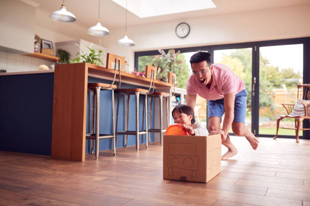 Asian Father And Son Pushing Son Around Kitchen Floor At Home In Junk Modelled Car stock photo