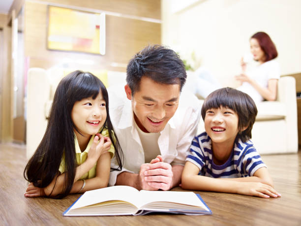 asian father and two children reading book - kultura wschodnioazjatycka zdjęcia i obrazy z banku zdjęć