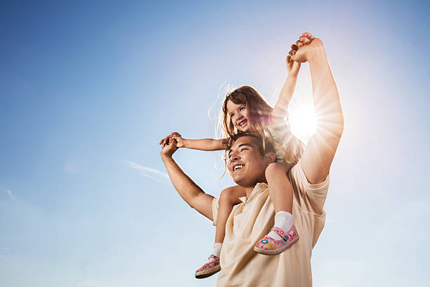 Asian father carrying daughter on shoulders against the blue sky. stock photo