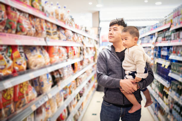 Asian father carrying his baby to a supermarket Asian father carrying his baby to a supermarket. snack aisle stock pictures, royalty-free photos & images